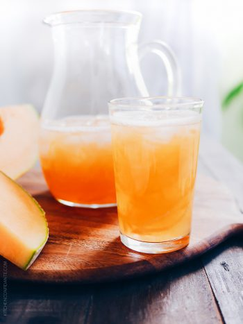 A pitcher and a glass full of icy cold cantaloupe juice.