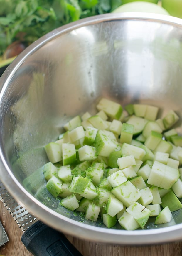 Chopped green apples in a metal bowl.