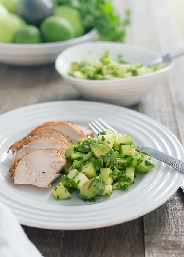 Green Apple Salsa Verde alongside sliced chicken on a white plate.