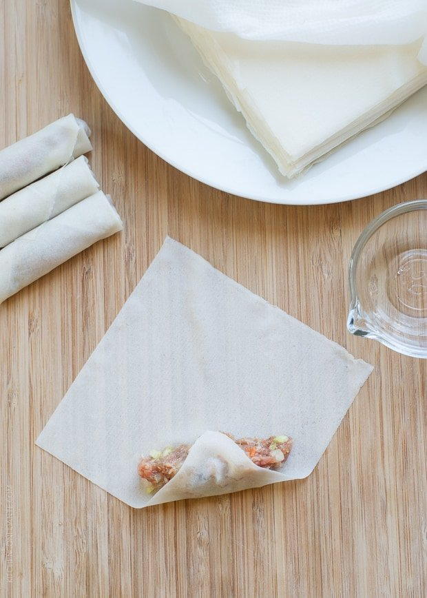 Lumpiang Shanghai - Filipino Spring Rolls (Lumpia) wrapper spread out with filling, showing how to begin rolling the lumpia