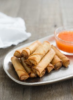 Lumpiang Shanghai - Filipino Spring Rolls (Lumpia) stacked on a platter with dipping sauce in the background