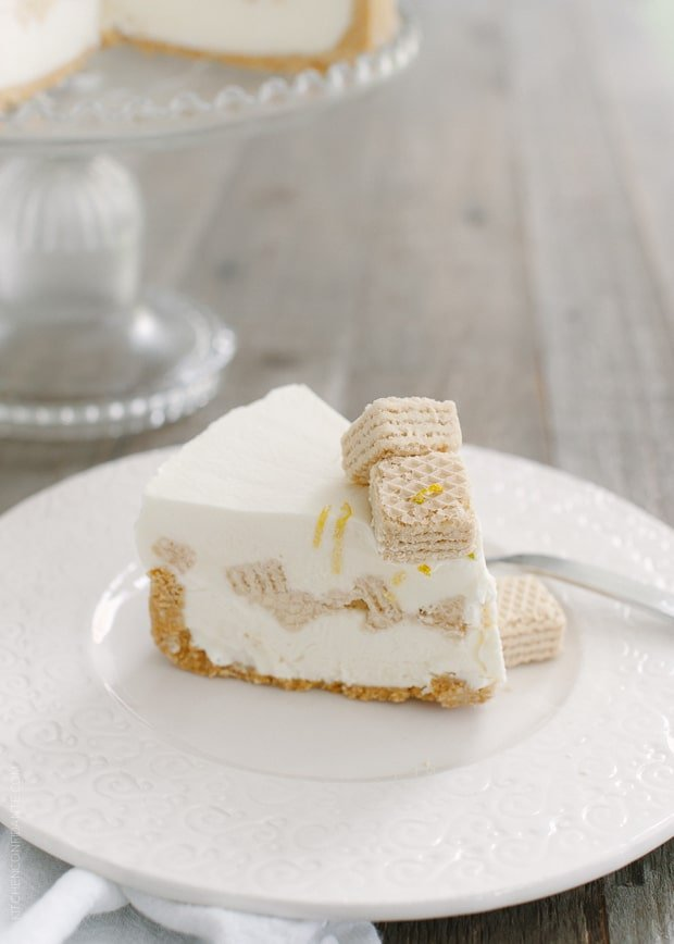 A slice of no-bake cheesecake layered with lemon wafers on a white plate.