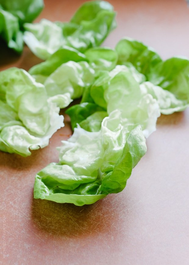Butter lettuce leaves on a cutting board.