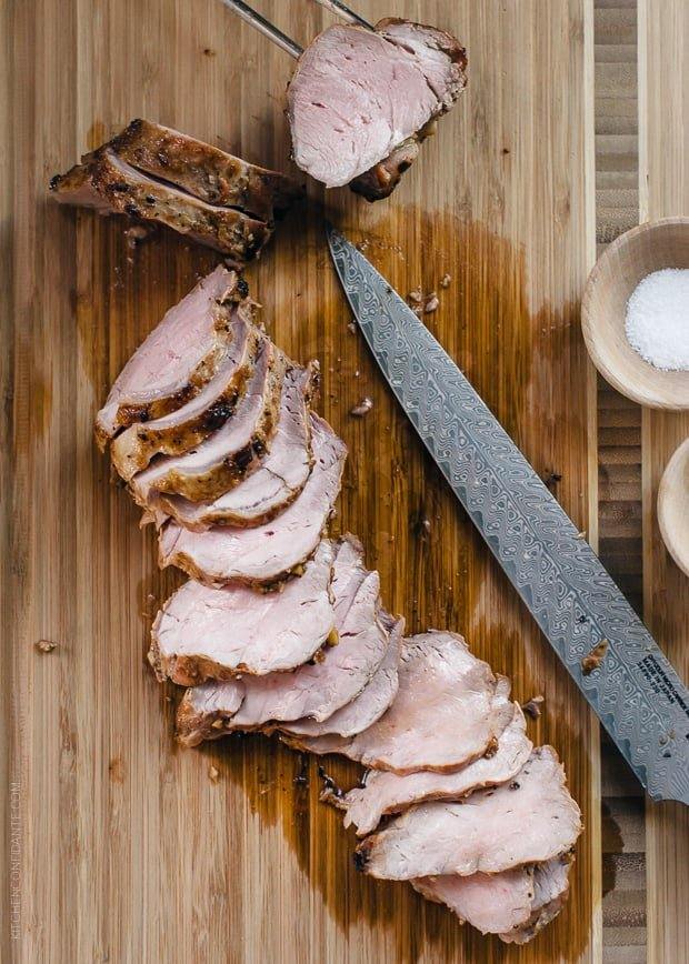Slices of Adobo-style Grilled Pork Tenderloin on a wooden cutting board.