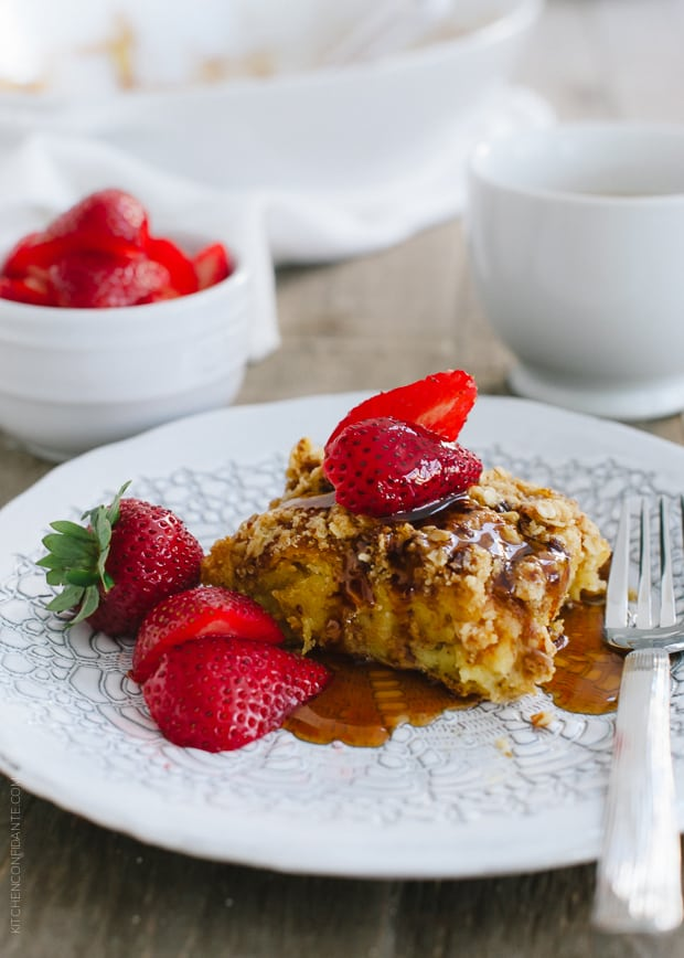 A piece of Baked Buttermilk French Toast with Oat Streusel topped with strawberries.
