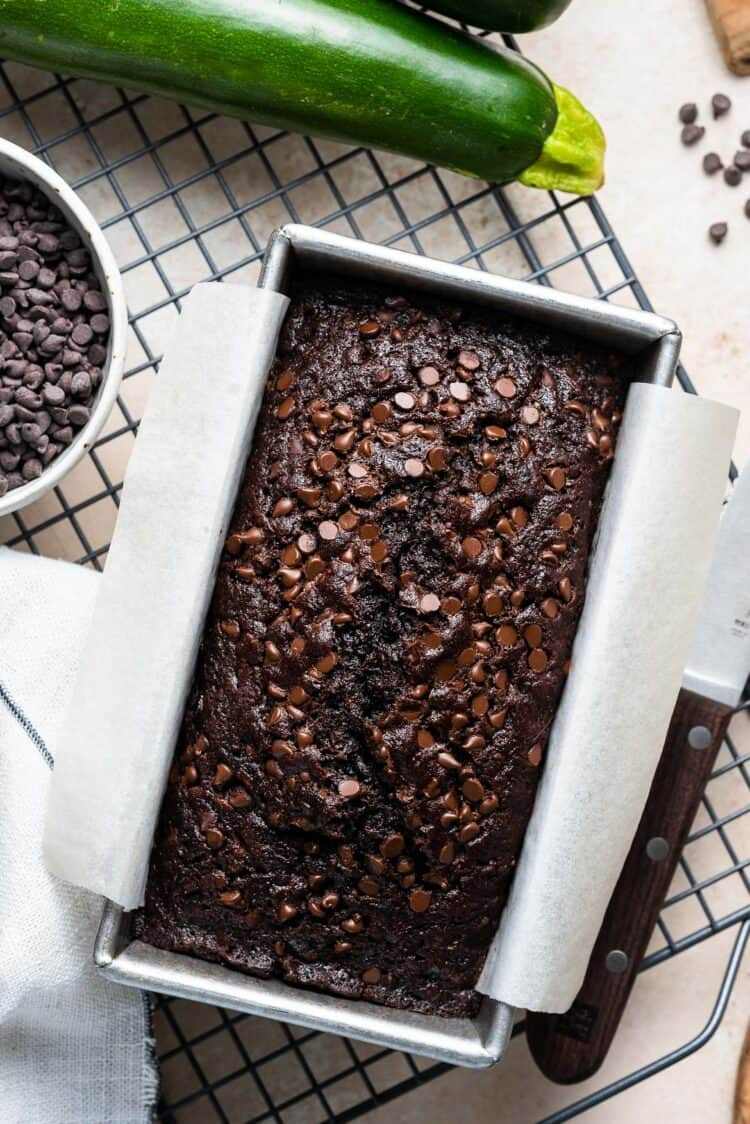 A loaf of Double Dark Chocolate Zucchini Bread on a cooling rack.