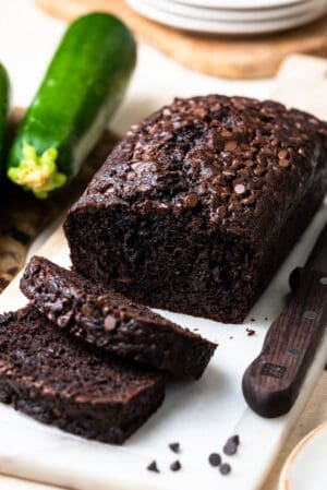Double Dark Chocolate Zucchini Bread sliced on a marble cutting board.