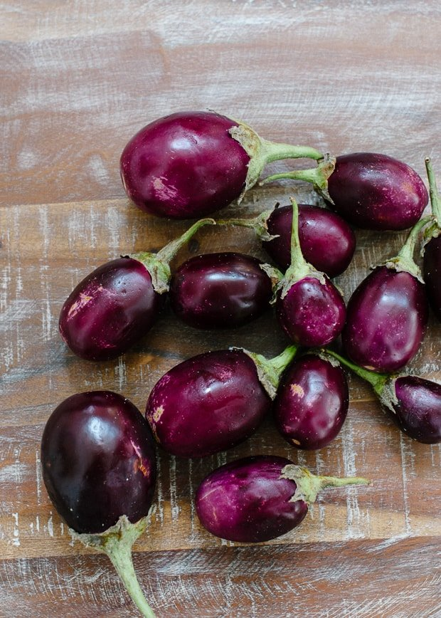 A variety of Indian eggplants on a wooden surface.