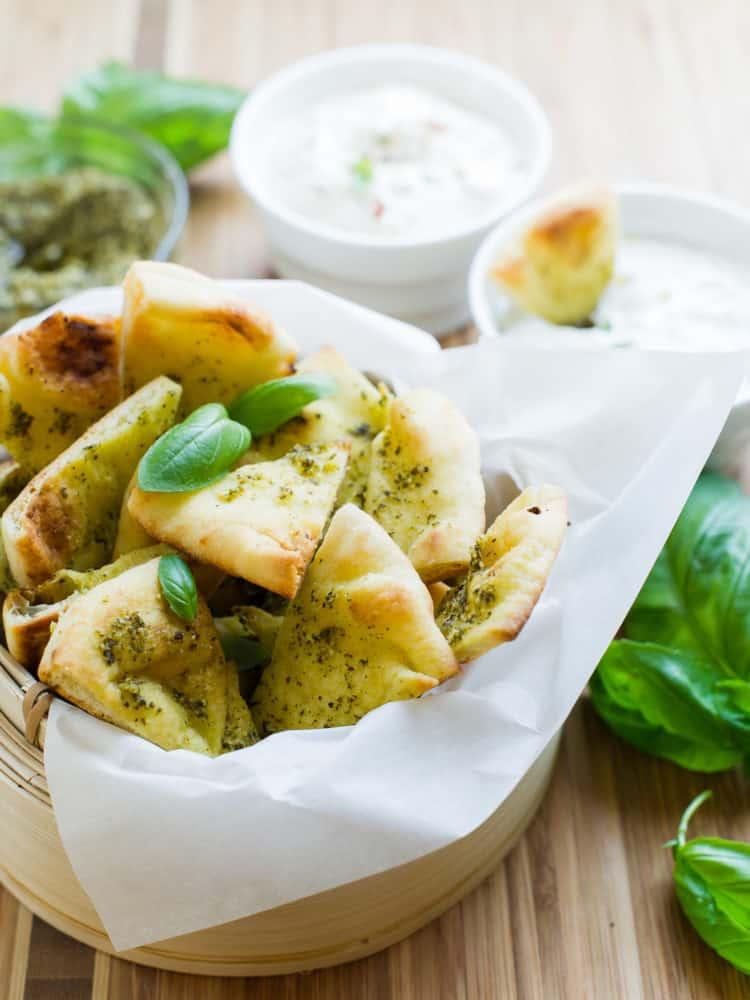 Basket of Pesto Baked Naan Chips with fresh basil garnish.