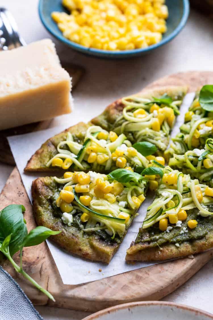 Zucchini, Corn and Pesto Flatbreads sliced on a wooden board.