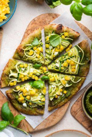 Zucchini, Corn and Pesto Flatbread sliced on a wooden board.