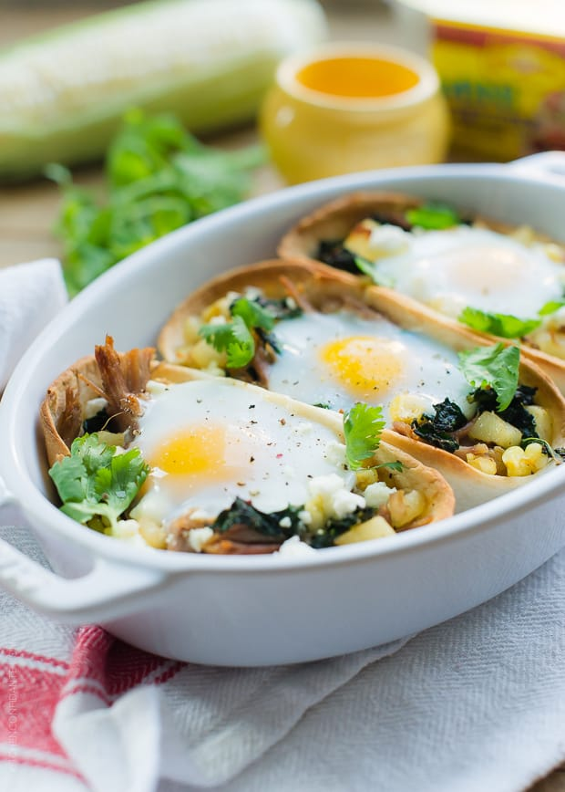 Eggs baked into tortilla shells filled with shredded pork, potatoes, and kale to make weeknight taco boats.