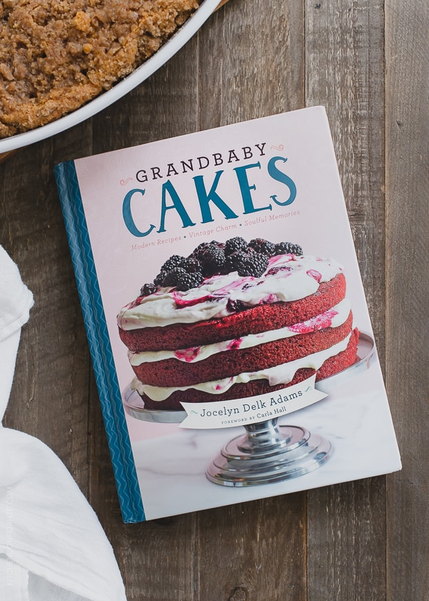 Grandbaby Cakes cookbook on a rustic surface with a sweet potato coffee cake in the background.