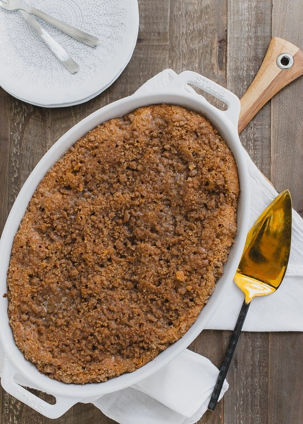 Buttered Rum and Candied Sweet Potato Crumb Cake baked in a white oval dish.