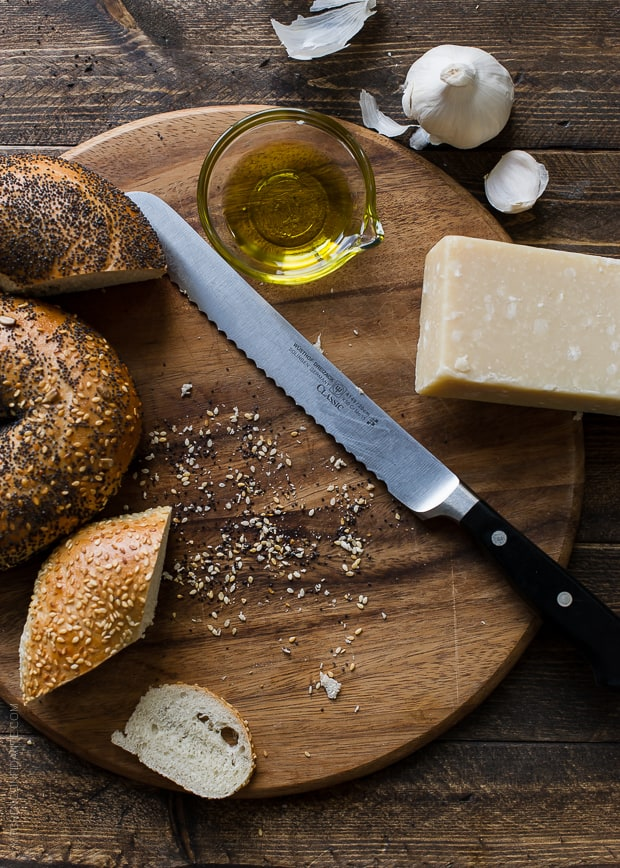 Sliced bagels alongside a serrated knife on a cutting board.