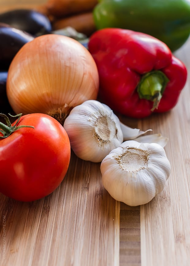 A tomato, onion, garlic and a red bell pepper on a wooden surface.