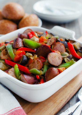 An 8x8 casserole dish filled with chopped sausage, eggplant, and peppers.