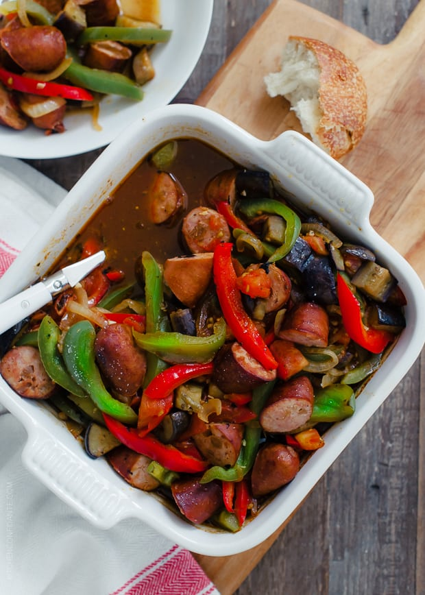 An 8x8 dish of Greek-Style Sausage and Peppers (or Spetzofai) served with crusty bread.