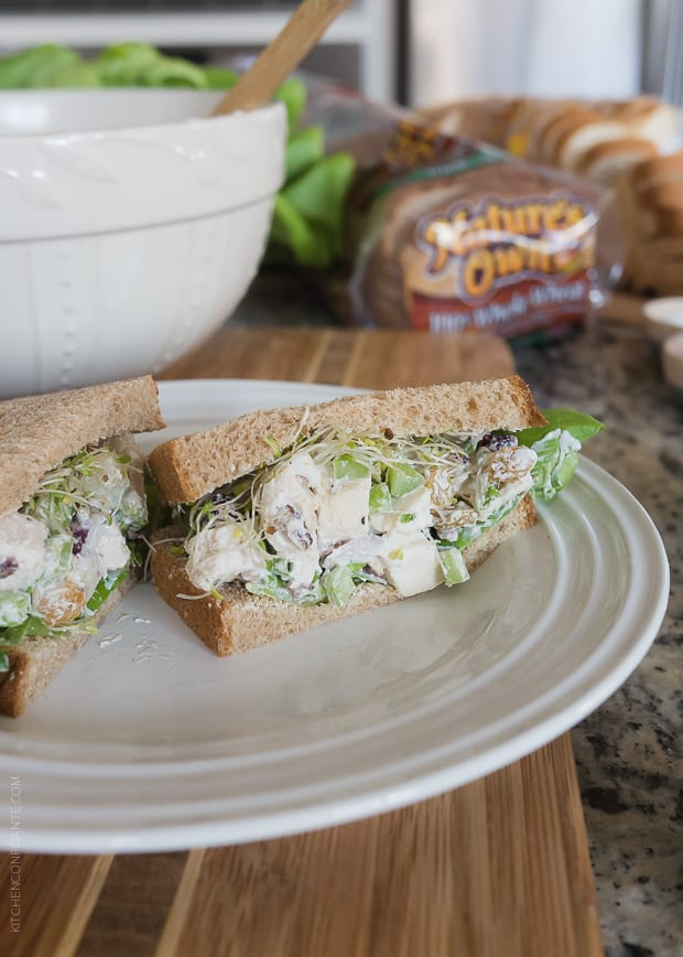 Green Apple Chicken Salad (Mayo Free) packed into a sandwich and served on a white plate.
