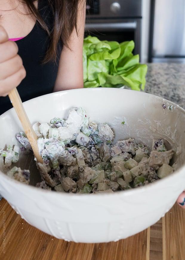 Stirring a bowl of Mayo Free Green Apple Chicken Salad.