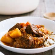 Mechado, a Filipino Beef Stew, served over a bed of rice in a white bowl.
