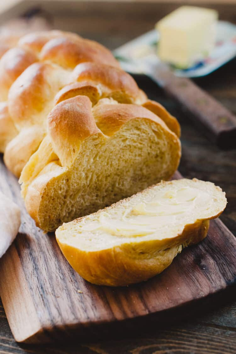 Loaf of Sweet Potato Challah sliced on a wooden cutting board.