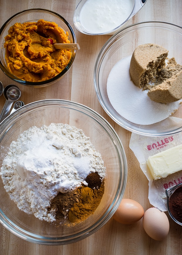 A bowl of pumpkin puree, a bowl of white and brown sugar, and a bowl filled with flour and spices on a counter top.