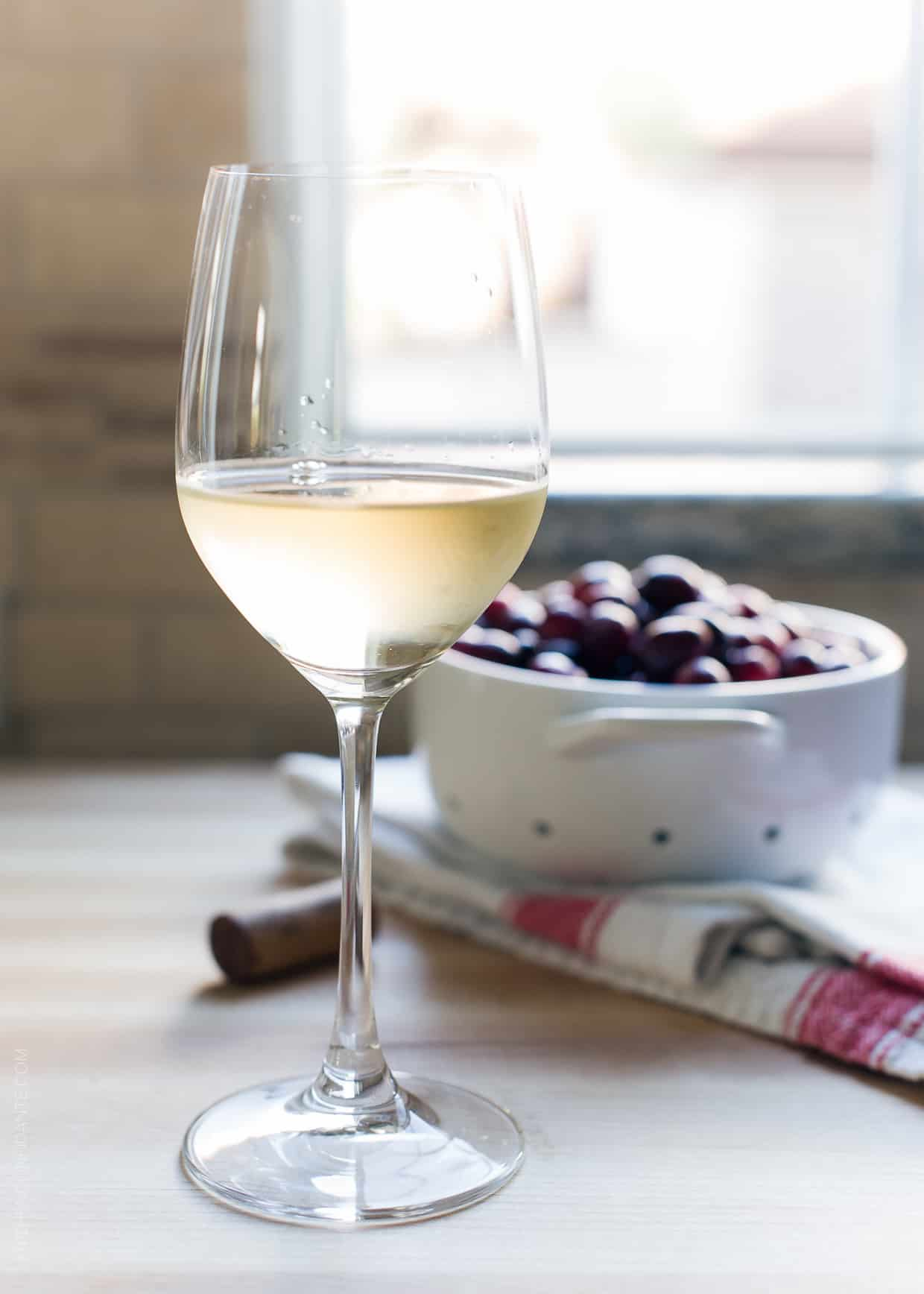 A glass of white wine with a bowl of cranberries in the background.