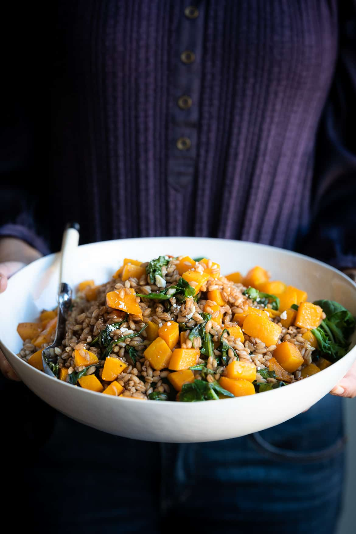 Roasted Butternut Squash Winter Salad with Kale, Farro and Cranberry Dressing in a white bowl.