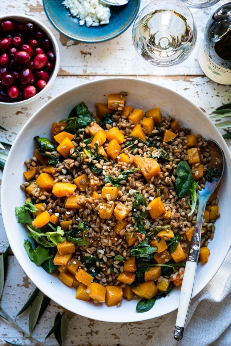 Roasted Butternut Squash Winter Salad in a white bowl on a wooden surface.