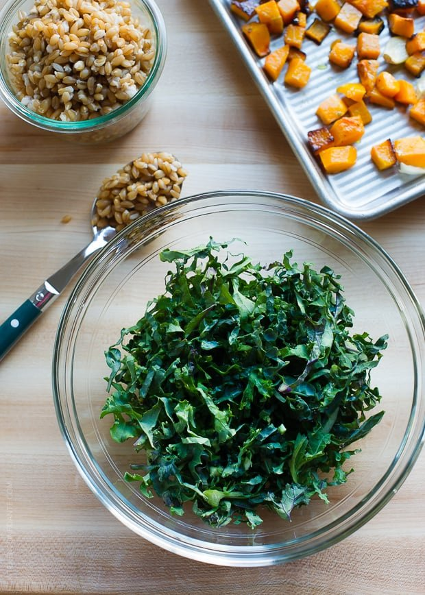 A glass bowl of kale, surrounded by farro and roasted butternut squash on a baking tray.