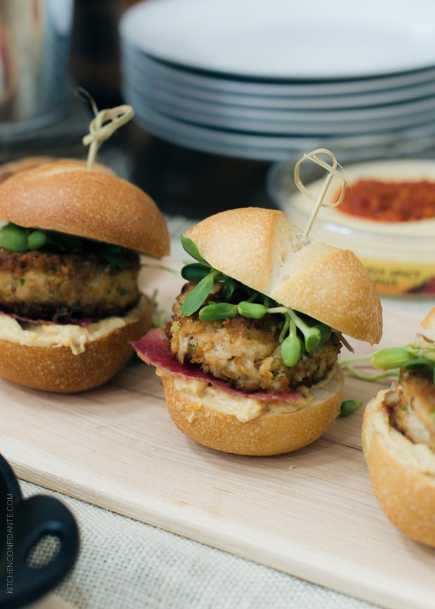 Pretzel Crusted Crab Cake Sliders in a row on a serving board.