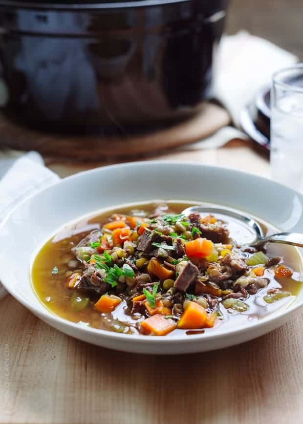 White bowl filled with Prime Rib Beef and Lentil Soup on a wooden surface.