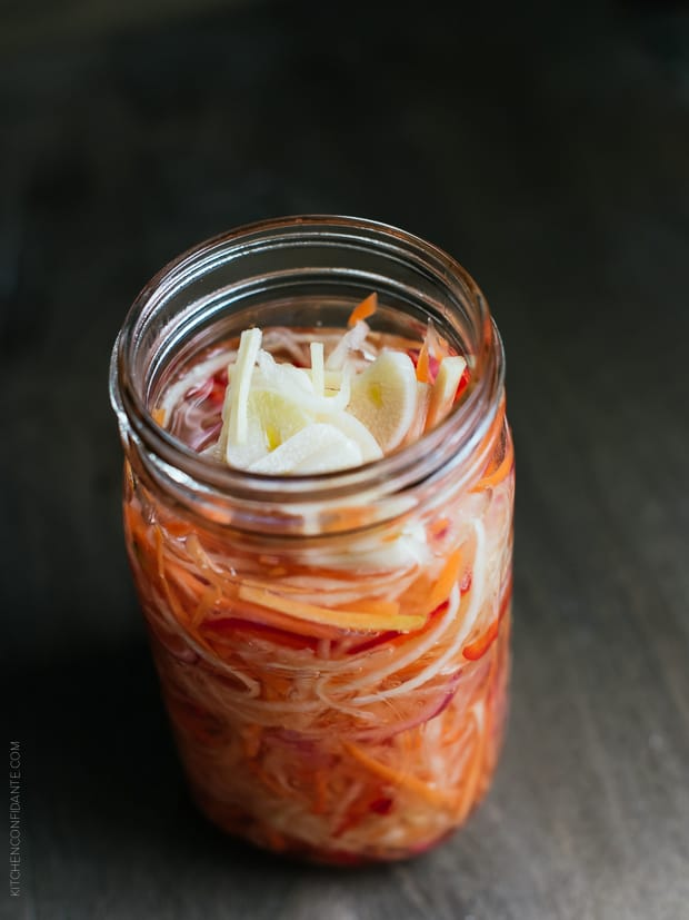 Glass jar filled with homemade Achara on a wooden surface.