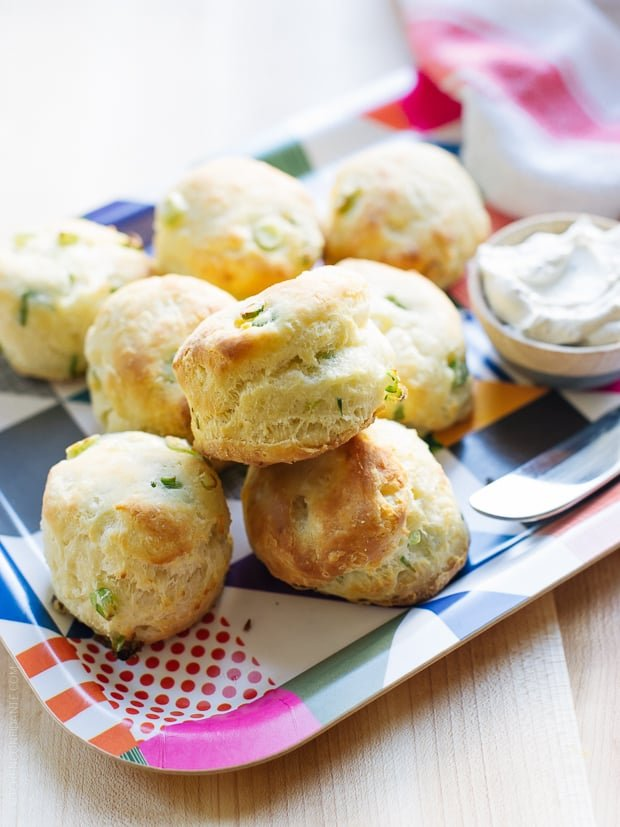 Cream Cheese and Green Onion Biscuits stacked on a serving platter.