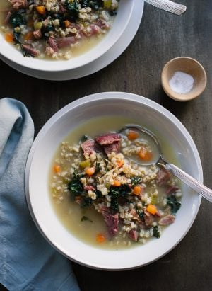 Two white soup bowls filled with Ham, Barley and Kale Soup made from a leftover ham bone.