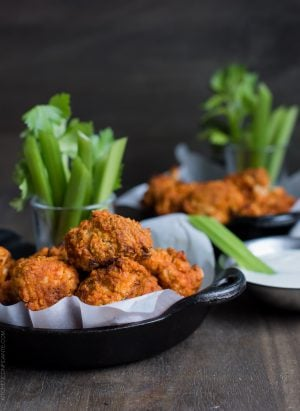 "Hummus Battered Buffalo Cauliflower ""Wings"" served in small cast iron skillets alongside stalks of celery."