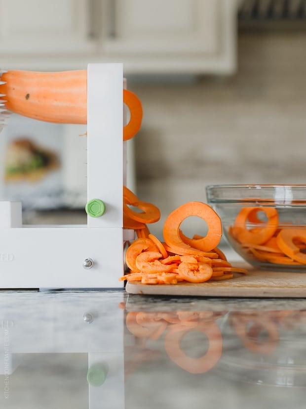 Using a spiralizer to make ribbons of sweet potato.