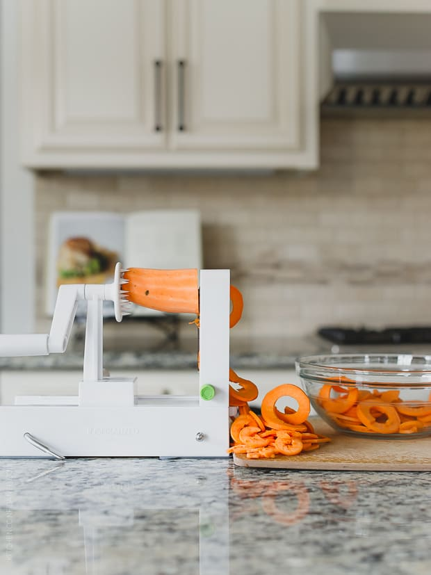 Spiralizing sweet potatoes in a kitchen.