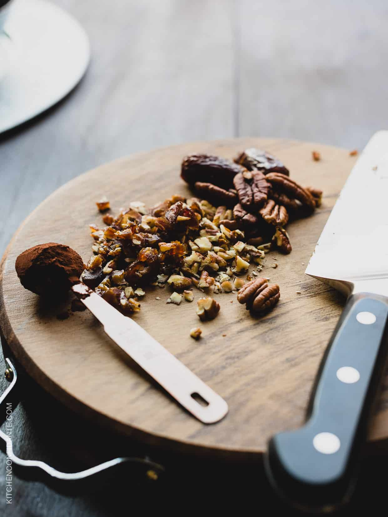 Chopped dates and pecans on a wooden cutting board.
