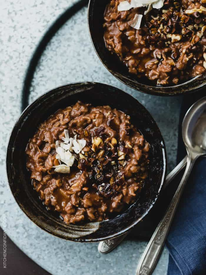 Two bowls of Chocolate Coconut Oat Porridge garnished with coconut and mini chocolate chips.