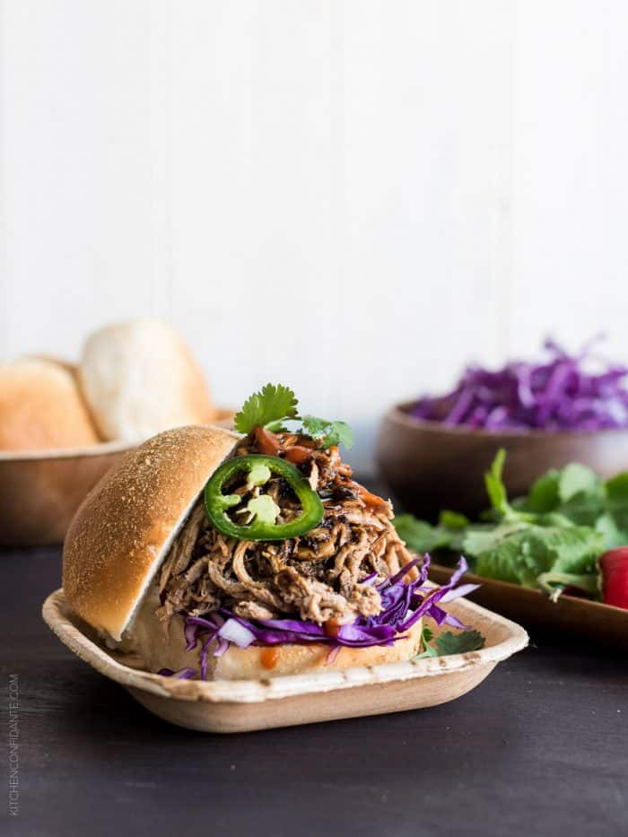 Filipino Adobo-style Pulled Pork Sandwich layered with red cabbage, a few leaves of cilantro and sriracha.