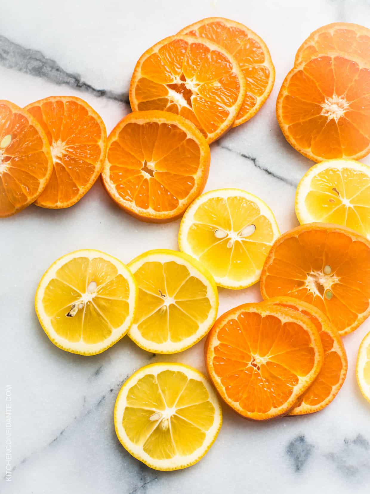 Slices of citrus fruit on a marble surface.