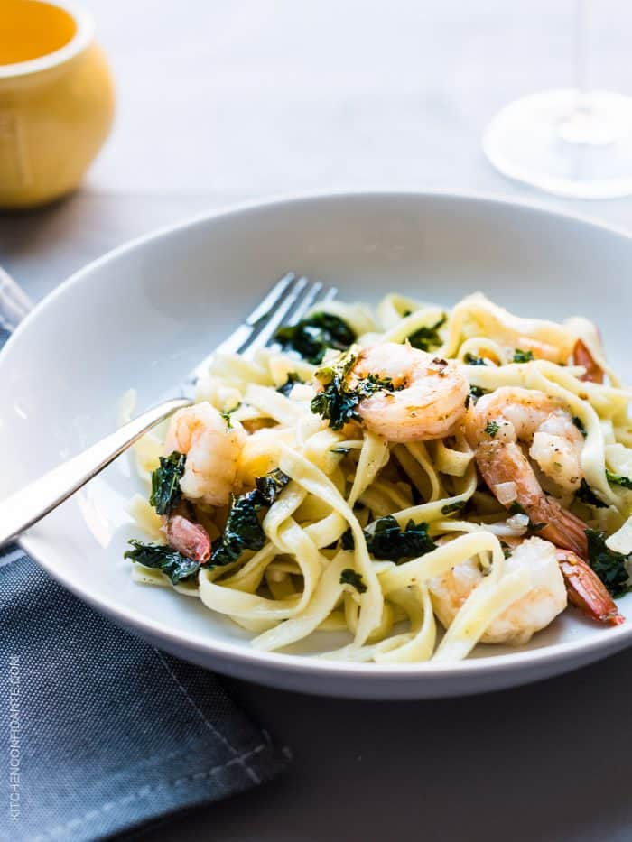 Freshly cooked linguine, leafy kale, and shrimp twirl together on a dinner plate to create Kale and Shrimp Scampi.