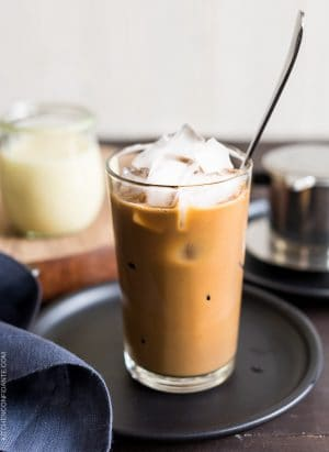A tall glass of Vietnamese Iced Coffee (Ca Phe Sua Da) with a spoon to stir.