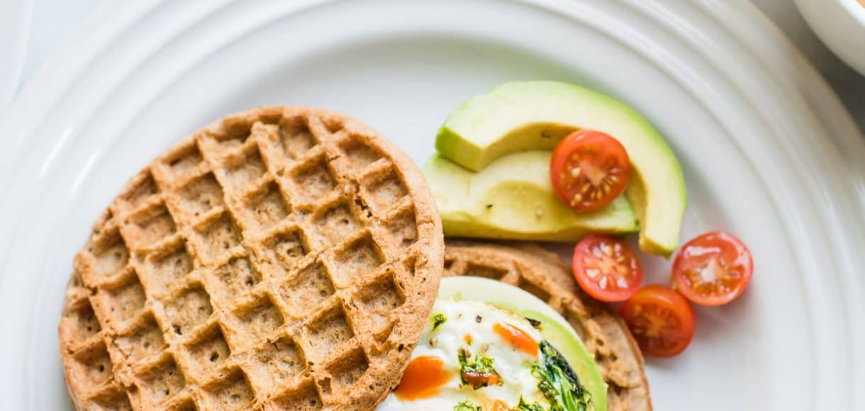 Two wholegrain waffles, one topped with an over easy egg, spinach, avocado, and hot sauce to form a Waffle Breakfast Sandwich.
