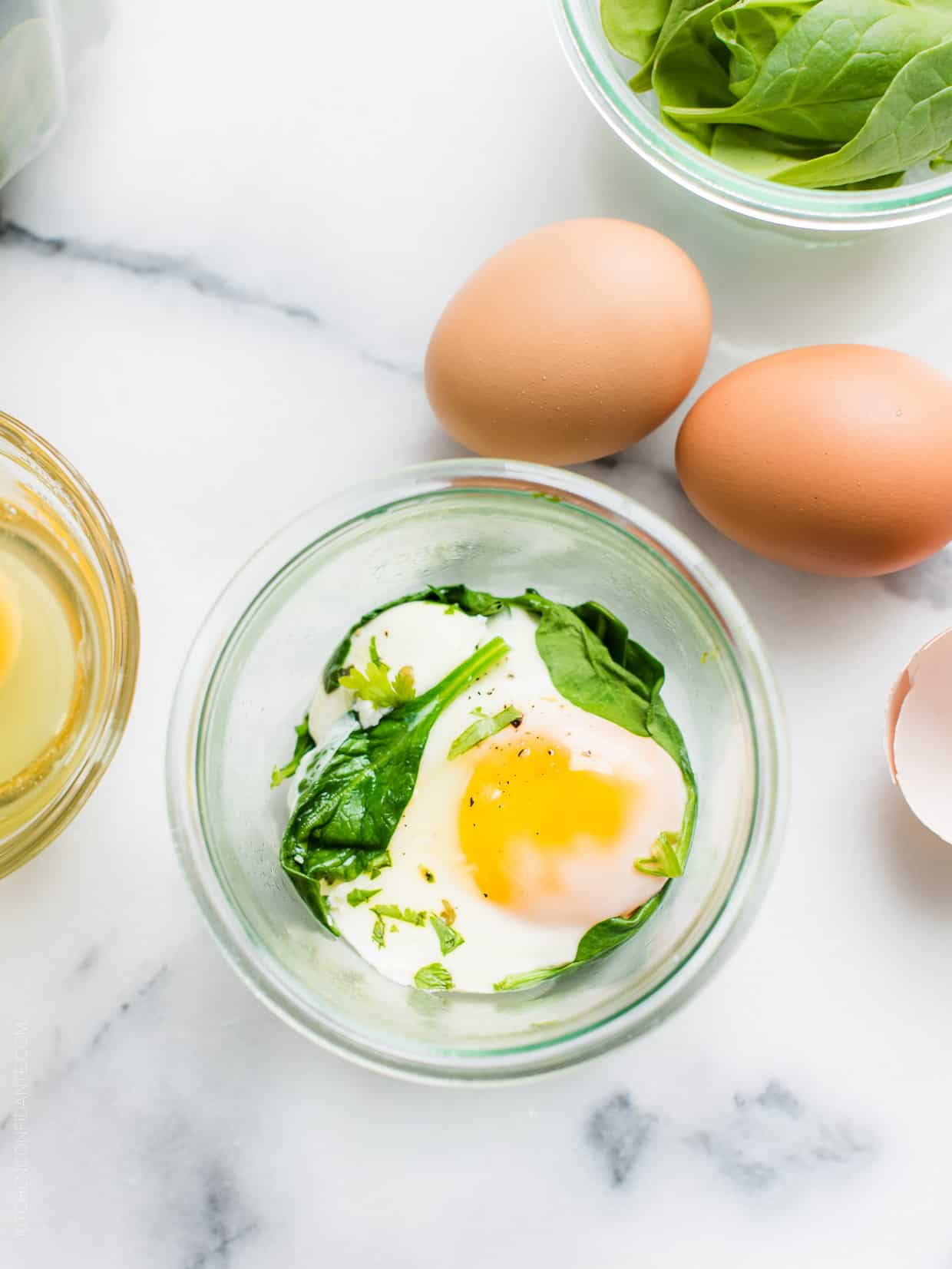 Egg and spinach in a mason jar surrounded by more fresh eggs on a marble surface.