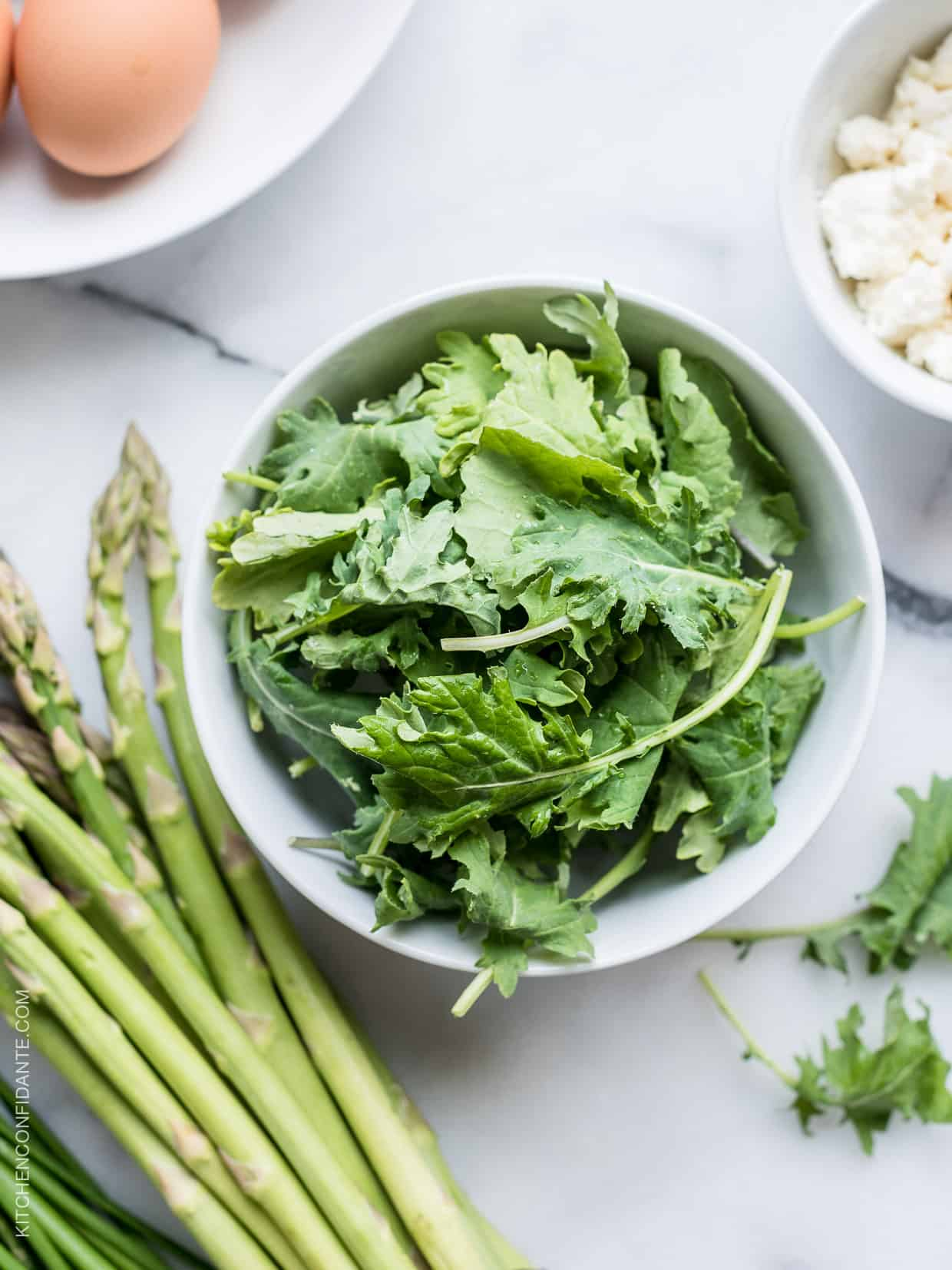 A white bowl filled with fresh kale alongside stalks of asparagus.
