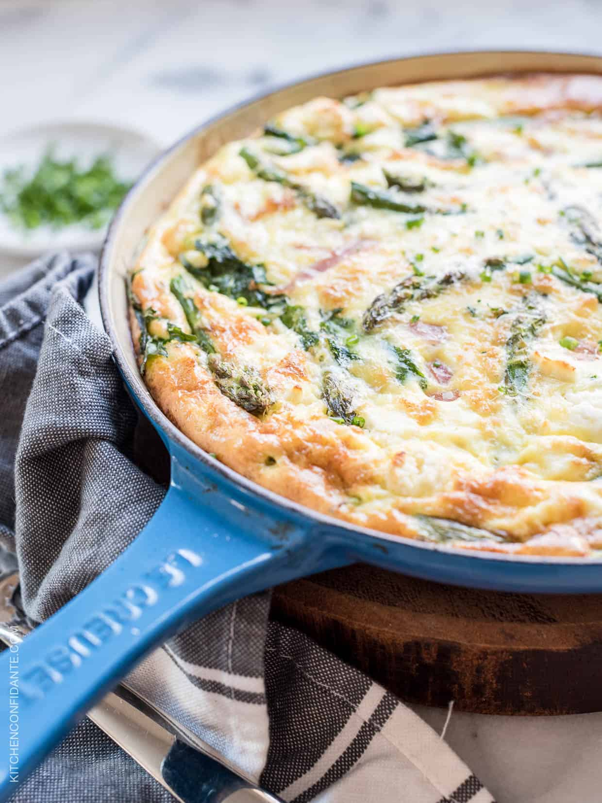 An Asparagus, Ham and Kale Frittata in a blue skillet.