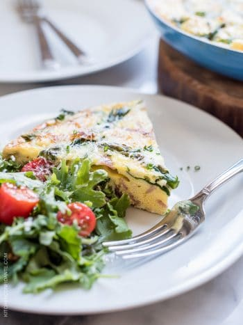 A wedge of Asparagus, Ham and Kale Frittata served on a white plate alongside a green salad.